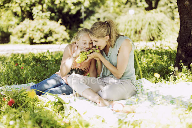 Girl and woman eating grapes in park — Stock Photo