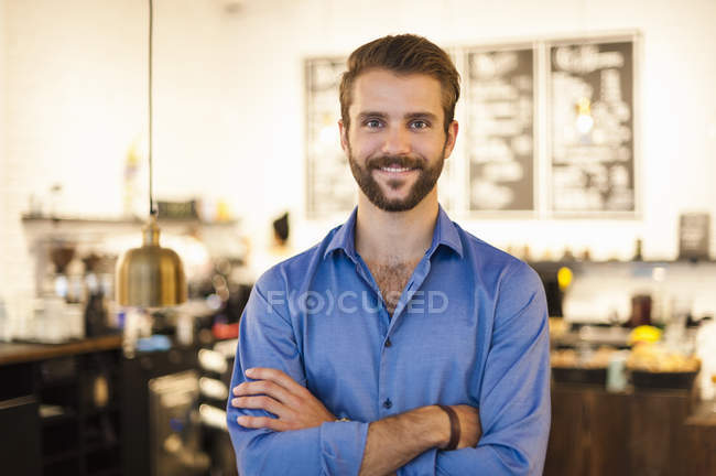 Portrait of confident young man standing in cafe with arms crossed — Stock Photo