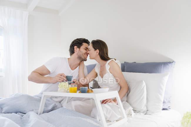 Couple au lit avec plateau de petit déjeuner — Photo de stock