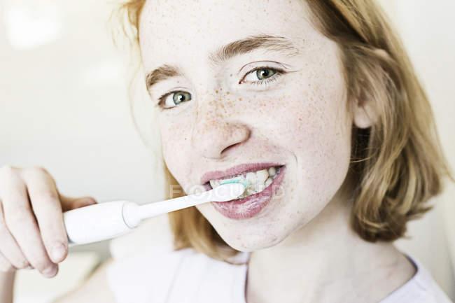 Portrait of smiling girl brushing teeth — Stock Photo