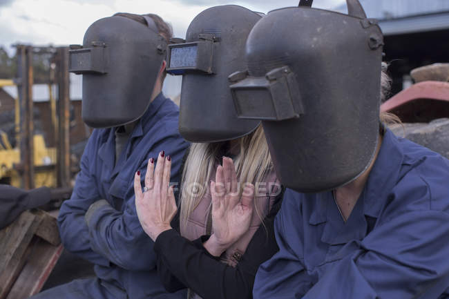 Three people wearing welding helmets sitting outdoors — Stock Photo