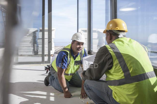 Два будівельниками обговорення на будмайданчик — стокове фото