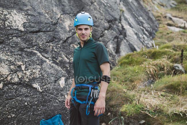 Портрет уверенного альпиниста, стоящего у скальной стены — стоковое фото