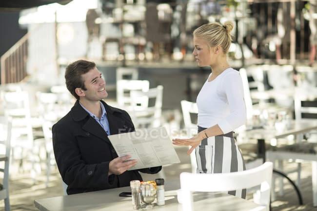 Caucasian man and waitress at outside restaurant — Stock Photo