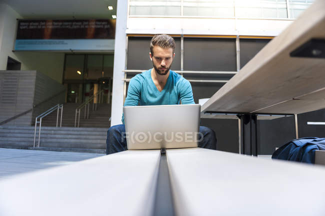 Young man sitting on bench and using laptop — Stock Photo