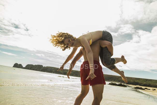 Brincalhão casal adolescente na praia — Fotografia de Stock