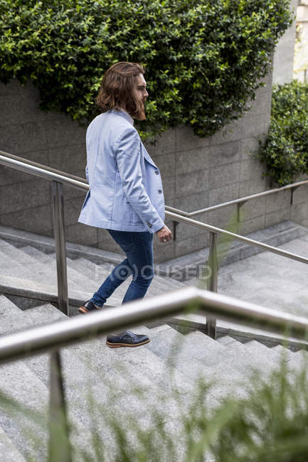 Businessman walking downstairs in city — Stock Photo