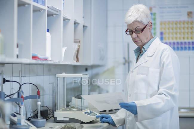 Старшая женщина в лаборатории смотрит на бумагу — стоковое фото