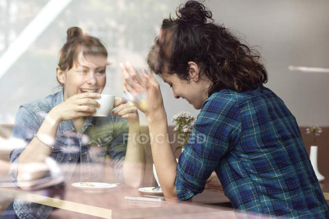 Two laughing women sitting behind windowpane of a coffee shop — Stock Photo