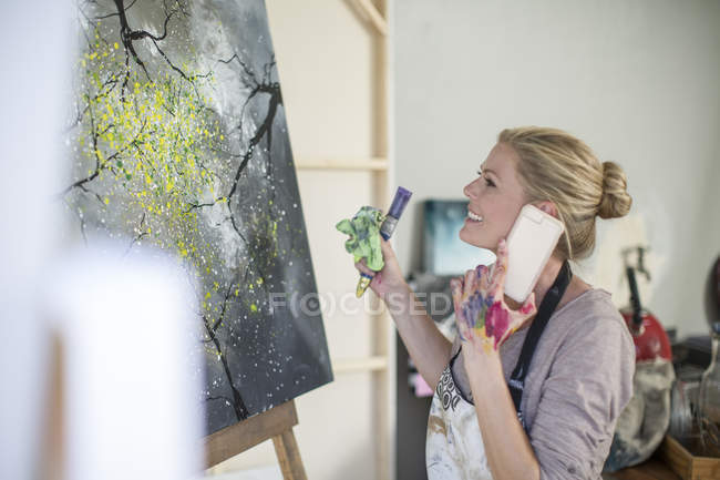 Female painter in front of canvas, smartphone — Stock Photo