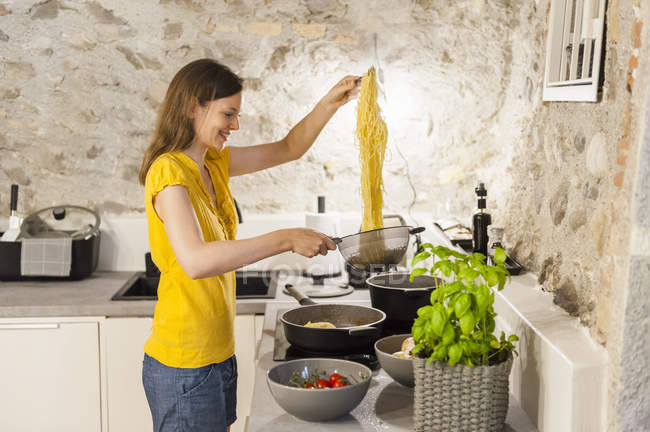 Woman preparing spaghetti in kitchen — Stock Photo