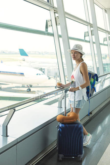 Vietnam, Ho Chi Minh, young woman with rolling  suitcase in airport — Stock Photo