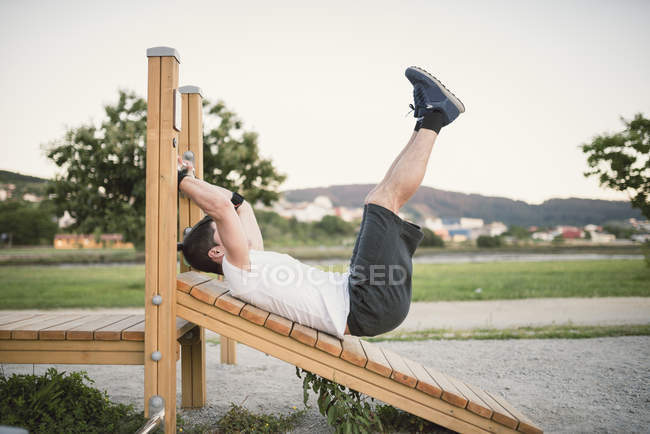Man doing sit-ups in park — Stock Photo