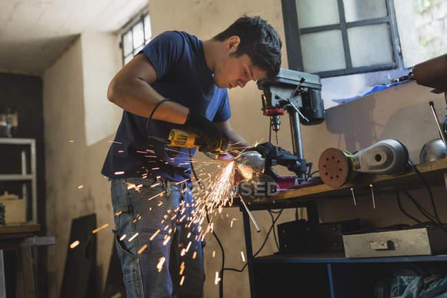 Fälscher Schleifen Metall im workshop — Stockfoto