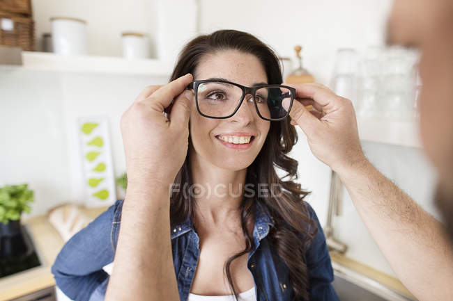 Man putting woman on oversized glasses — Stock Photo