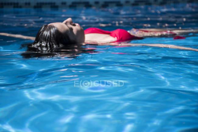 Mulher flutuando na água de uma piscina — Fotografia de Stock