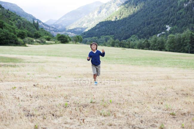 Happy little boy running on a mountain meadow — Stock Photo