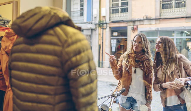 Two smiling women looking at shop window of a boutique — Stock Photo