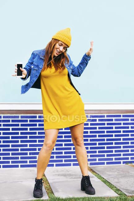 Dançando jovem mulher vestindo boné amarelo e vestido — Fotografia de Stock