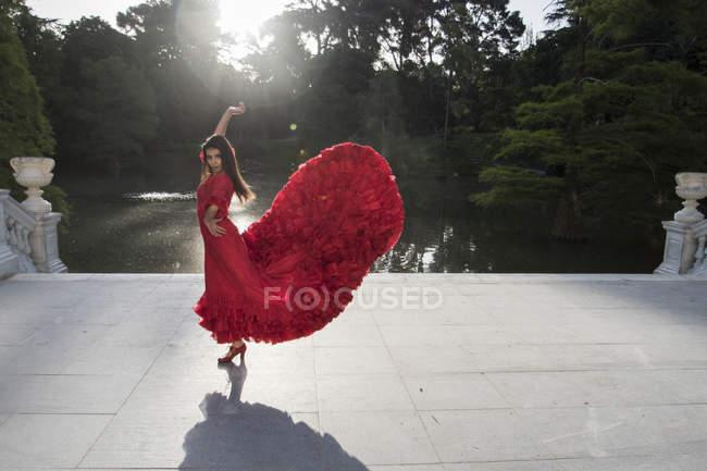 Жінка, одягнена в червону танці фламенко на терасі перед озеро — стокове фото