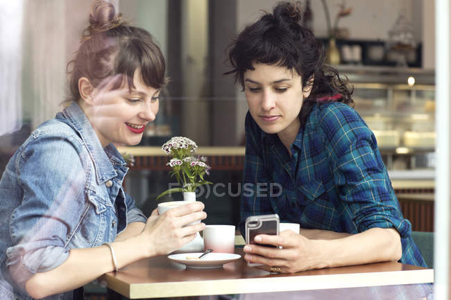 Two women sitting behind windowpane of a coffee shop looking at smartphone — Stock Photo