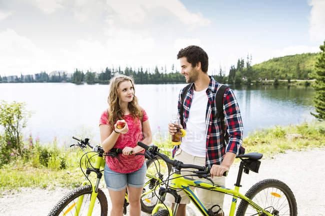 Jovem casal fazendo uma pausa na viagem de bicicleta — Fotografia de Stock