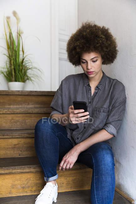 Giovane donna seduta sulle scale guardando smartphone — Foto stock