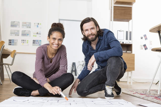 Portrait of two smiling colleagues on office floor with construction plan — Stock Photo