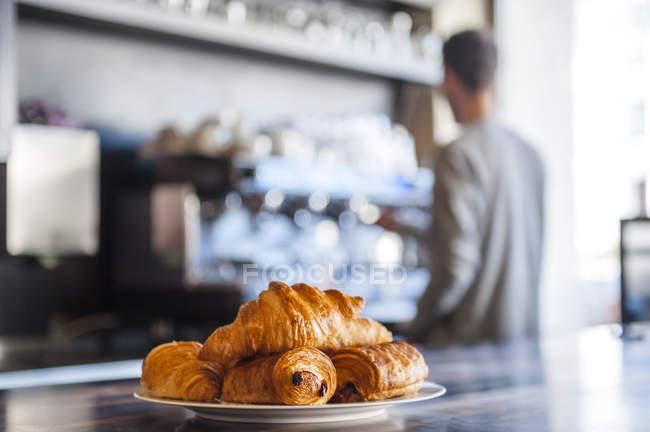 Croissants em placa no balcão de um café, a barista no fundo — Fotografia de Stock