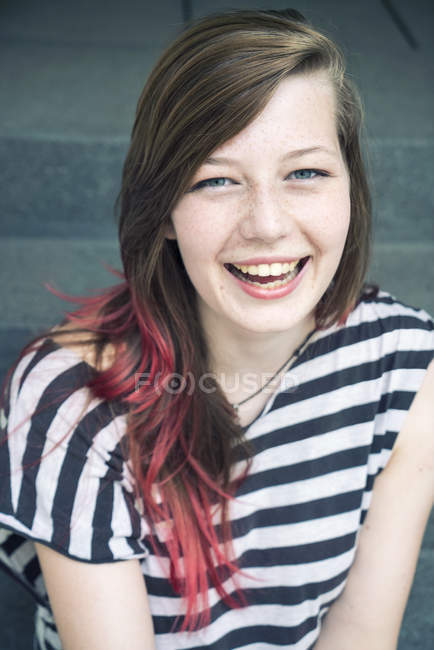 Portrait of laughing young woman with red strand of hair — Stock Photo