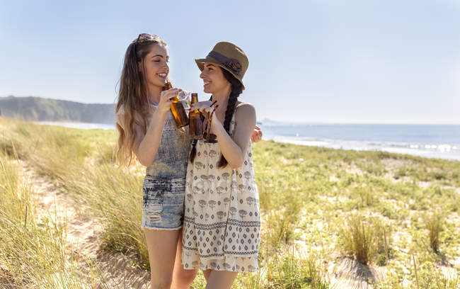 Two friends with beer bottles relaxing on beach — Stock Photo