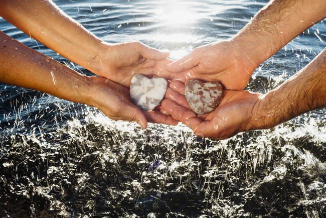 Hands holding stones — Stock Photo
