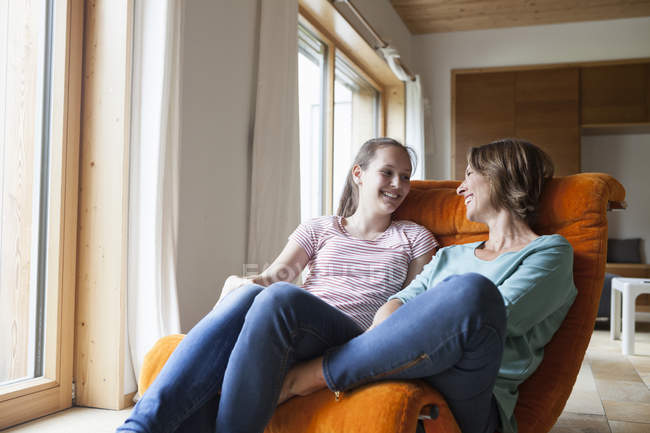 Happy mother and daughter sitting in armchair at home — Stock Photo