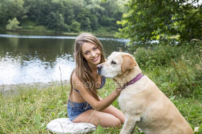 Жінка з собакою, сидячи на березі озера — стокове фото