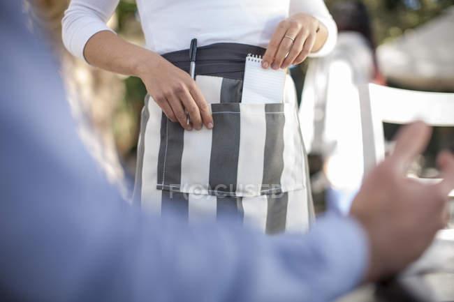 Serveuse en tenant le stylo et bloc-notes de tablier, vue partielle — Photo de stock