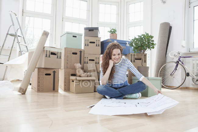Woman surrounded by cardboard boxes sitting on floor looking at construction plan — Stock Photo