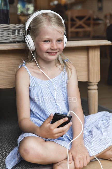 Portrait of happy little girl listening music with headphones and smartphone — Stock Photo