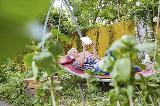 Donna rilassante su altalena in giardino — Foto stock