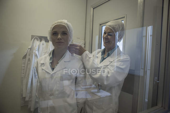 Two lab technicians putting on sterile protective clothing — Stock Photo