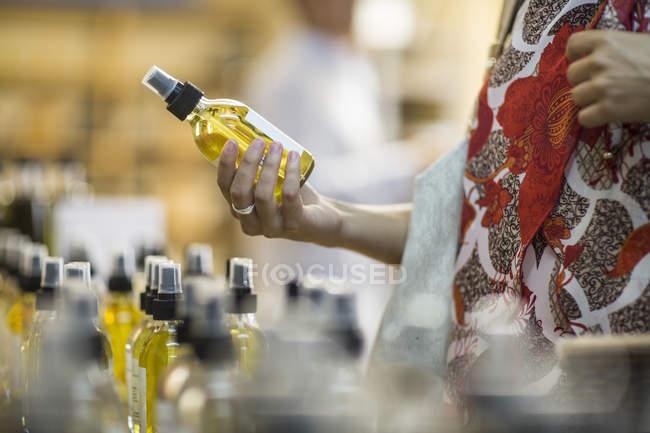 Крупный план женщины с бутылкой аромата в магазине — стоковое фото