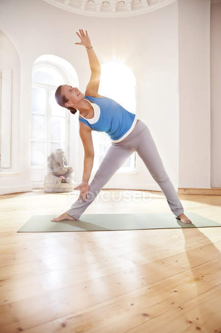 Woman in extended triangle pose in sunny yoga studio — Stock Photo