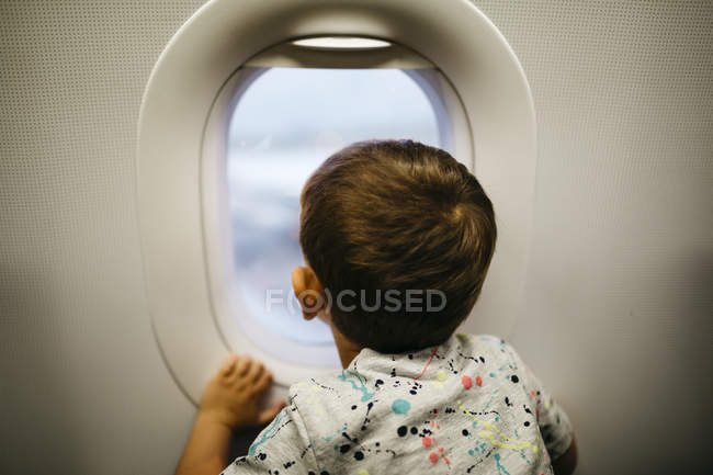Little boy looking out of airplane window — Stock Photo