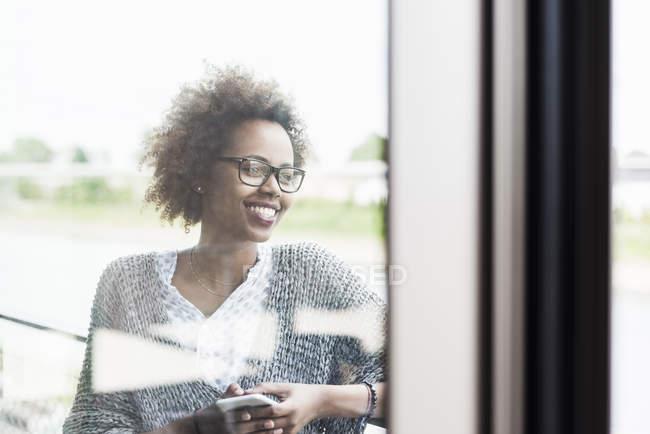 Mujer con smartphone que está parado en el balcón - foto de stock