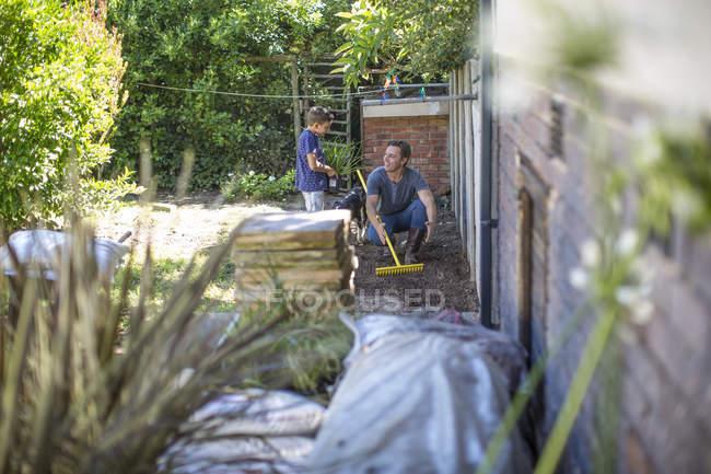 Батько і син, що працюють разом в саду — стокове фото