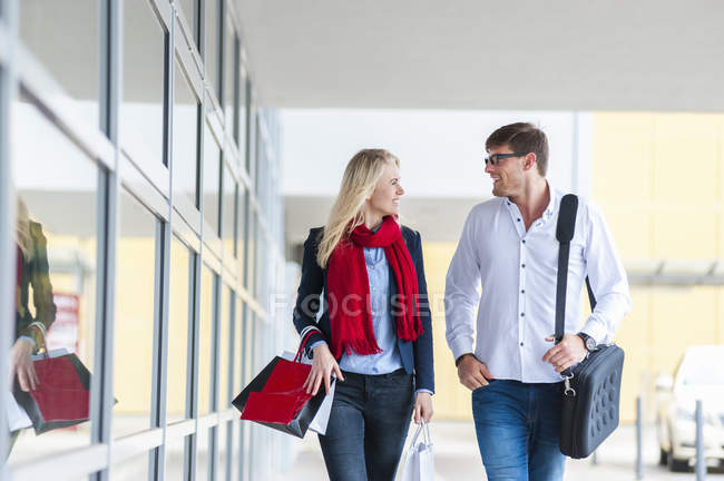 Smiling couple with bags passing urban building — Stock Photo