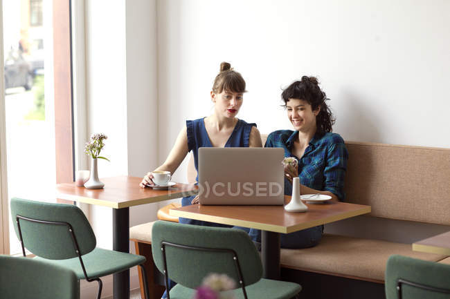 Two friends sitting in a coffee shop looking at laptop — Stock Photo