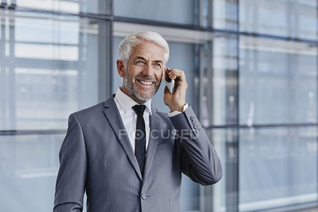 Smiling businessman on cell phone in modern office — Stock Photo