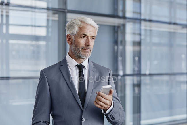 Confident businessman holding cell phone in modern office — Stock Photo