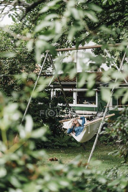 Donna al telefono rilassante in amaca — Foto stock