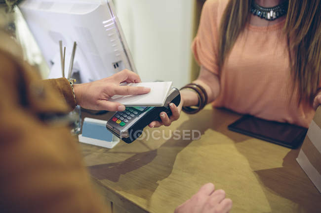 Woman paying using smartphone with NFC technology in a store — Stock Photo